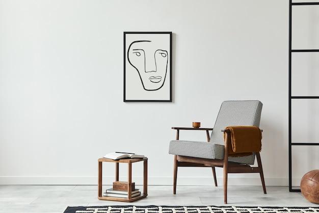 Composizione minimalista del soggiorno con poltrona di design, sgabello in legno, decorazione, cornice per poster finta nera, libro e accessori personali nell'arredamento moderno della casa. muro bianco. modello.