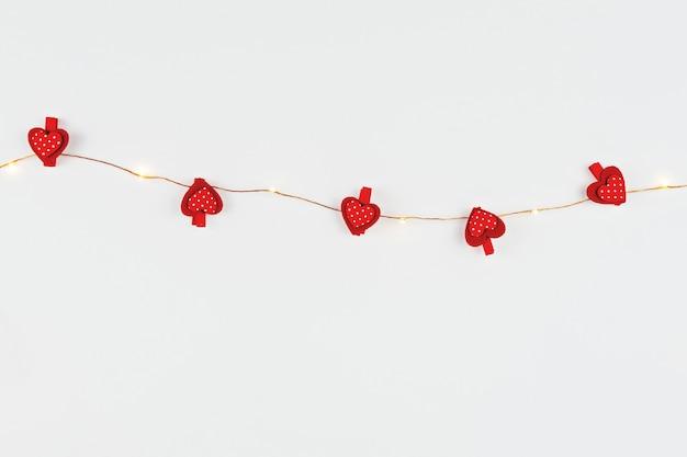 Composizione minimalista con luce fata e cuori rossi su bianco