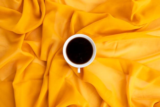 Concetto minimalista. caffè sulla sciarpa gialla background.autumn, concetto di autunno. disposizione piana, vista dall'alto, copia spazio