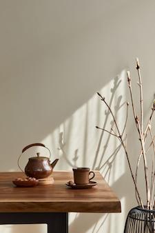Concetto minimalista dell'interno della sala da pranzo con tavolo familiare in legno, tazza di caffè, brocca da tè, stoviglie, parete beige e accessori personali. copia spazio..