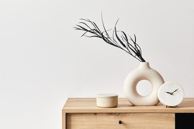 Concetto minimalista dell'interno del soggiorno in un elegante appartamento con comò in legno, foglia in vaso di ceramica, orologio ed eleganti accessori personali nell'arredamento moderno della casa. copia spazio. modello. .