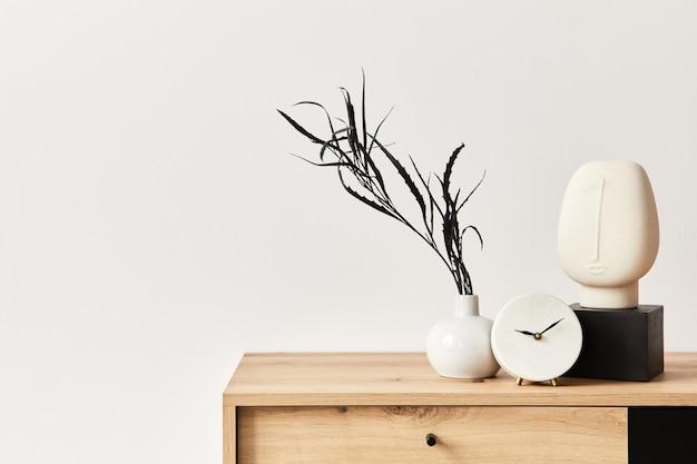 Concetto minimalista dell'interno del soggiorno in un elegante appartamento con comò in legno, foglia in vaso di ceramica, orologio ed eleganti accessori personali nell'arredamento moderno della casa. copia spazio.. .