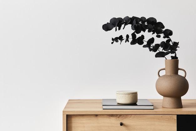 Concetto minimalista dell'interno del soggiorno in un elegante appartamento con comò in legno, foglia in vaso di ceramica ed eleganti accessori personali nell'arredamento moderno della casa. copia spazio.