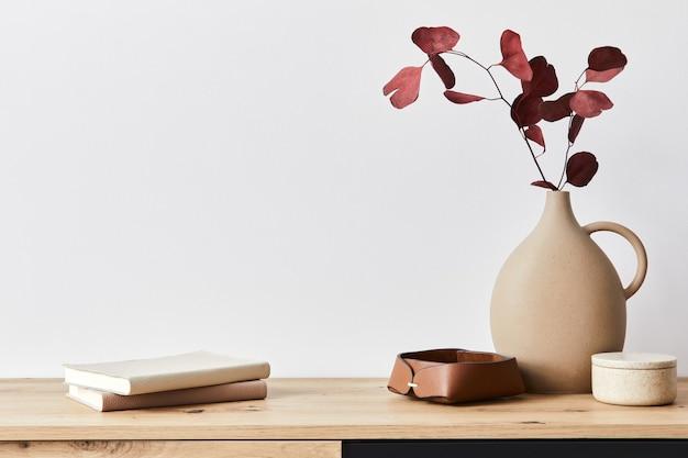 Concetto minimalista dell'interno del soggiorno in un elegante appartamento con comò in legno, foglia in vaso di ceramica ed eleganti accessori personali nell'arredamento moderno della casa. copia spazio.. .