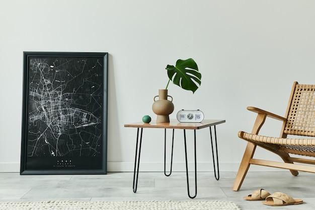 Concetto minimalista dell'interno del soggiorno con poltrona in rattan, tavolino da caffè in noce, foglia tropicale in vaso, orologio, mappa poster nera finta e accessori personali in un elegante arredamento per la casa
