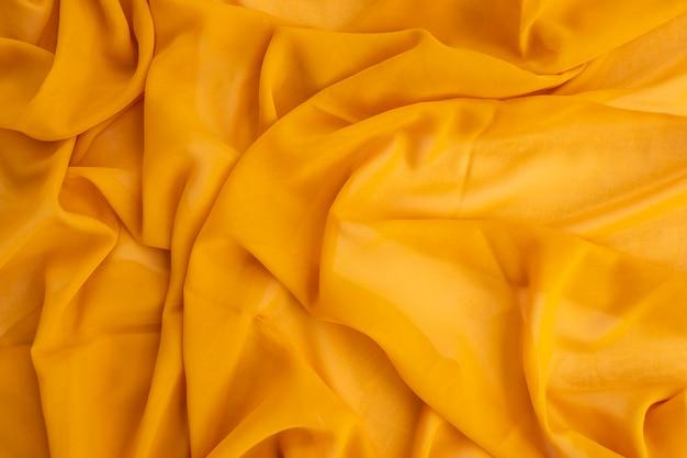 Concetto minimalista. fondo giallo di struttura della sciarpa. autunno, concetto di autunno. disposizione piana, vista dall'alto, copia spazio