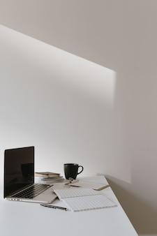 Area di lavoro minimalista della scrivania dell'ufficio domestico. computer portatile sul tavolo con tazza di caffè, foglio di carta, cancelleria contro il muro bianco