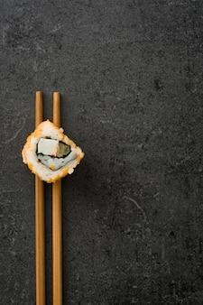 Sushi giapponesi minimalisti dell'alimento con la bacchette sulla vista superiore dell'ardesia nera