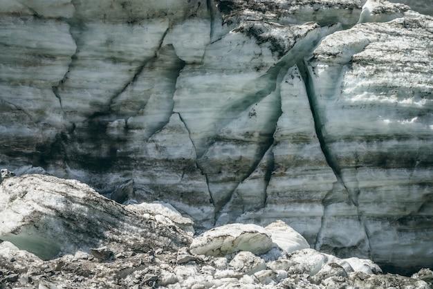 Sfondo di natura minimalista della superficie del ghiacciaio con crepe e graffi. sfondo naturale minimo di parete ghiacciata e blocchi di ghiaccio dal ghiacciaio da vicino. bella struttura della natura della parete glaciale lucida.