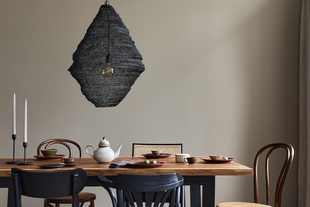 Concetto rustico minimalista dell'interno della sala da pranzo con tavolo familiare in legno, sedie retrò di design, tazza di caffè, decorazione, lampada pedante e accessori personali in un elegante arredamento per la casa..