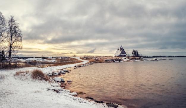 Paesaggio invernale innevato minimalista con autentica casa sulla riva nel villaggio russo rabocheostrovsk.