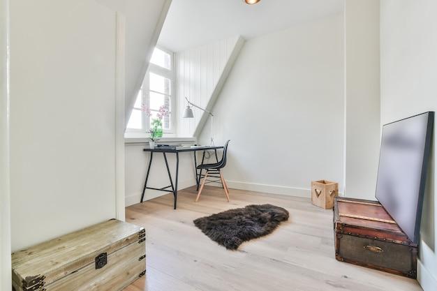 Luogo di lavoro domestico in stile minimalista con tavolo e sedia posizionati vicino alla finestra in una piccola mansarda con cassapanche in legno antiquate e pittura