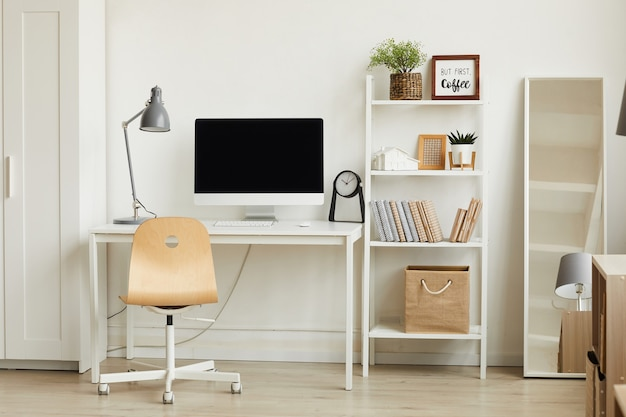 Interno appartamento minimalista con focus sulla scrivania del computer contro il muro bianco