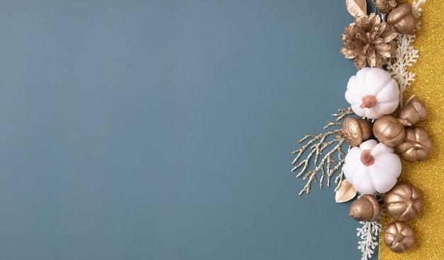 Banner autunnale minimalista con copia spazio e ghiande dorate, coni, foglie e zucche su uno sfondo colorato.