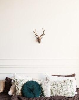 Interno minimalista della camera da letto. letto con cuscini e cervo decorativo appeso al muro