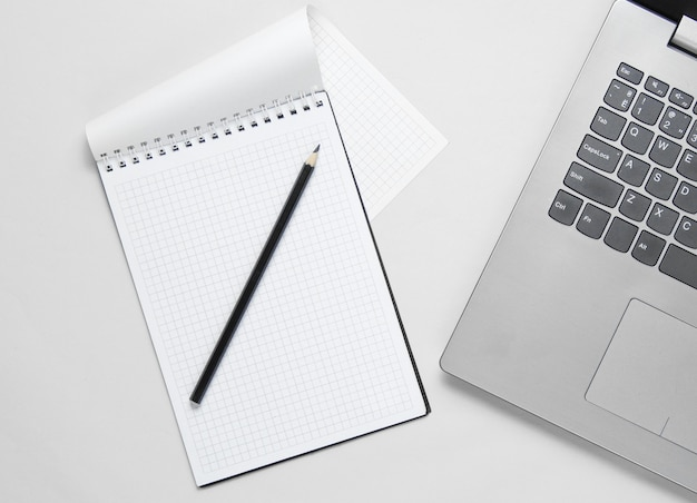 Concetto di business minimalista. computer portatile, taccuino con la matita su bianco