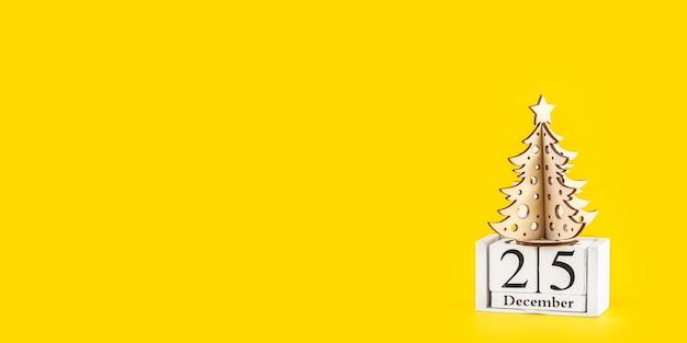 Albero di natale minimalista su sfondo giallo pastello alla moda. buon natale e felice anno nuovo biglietto di auguri con copia spazio. concetto di vacanza invernale. banner lungo e largo.