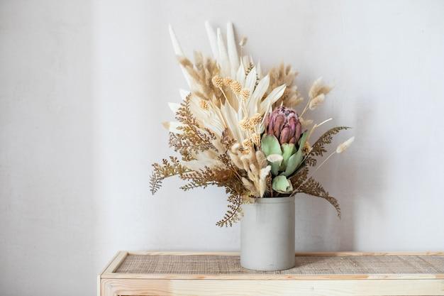 Composizione minimalista di fiori secchi in vaso cilindrico in ceramica come decorazione domestica.