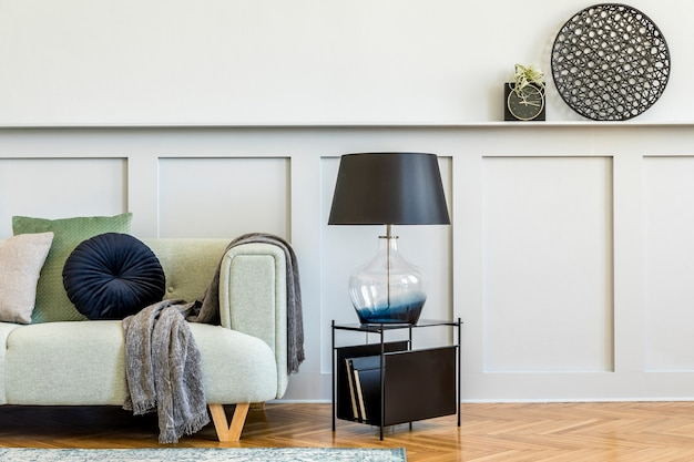 Composizione minimalista del soggiorno con divano di design, tavolino, pianta d'aria, libri, decorazioni, cuscini, plaid, moquette, pannelli in legno ed eleganti accessori personali in un elegante arredamento per la casa.