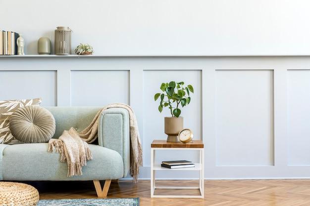 Composizione minimalista del soggiorno con divano di design, tavolino, pianta, libri, decorazioni, cuscini, plaid, moquette, pannelli in legno ed eleganti accessori personali in un elegante arredamento per la casa.