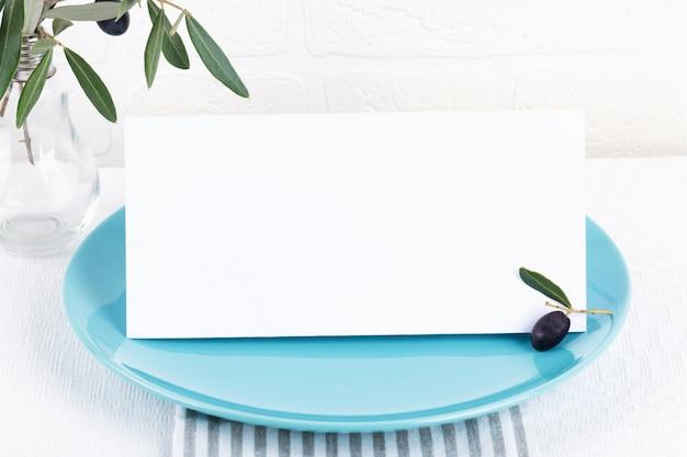 Composizione minimalista con biglietti per invito, menu, segnaposto su un piatto di porcellana blu pastello con rami di ulivo