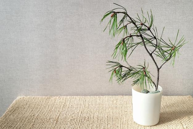 Composizione minimalista con rametto di pino in stile ekibana giapponese