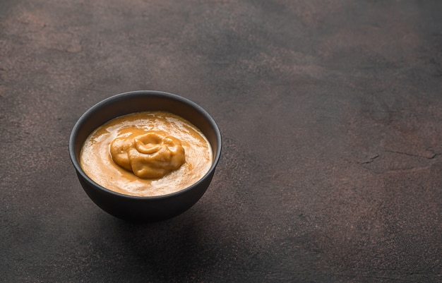 Sfondo culinario minimalista con senape su uno sfondo marrone. vista laterale con copia spazio.