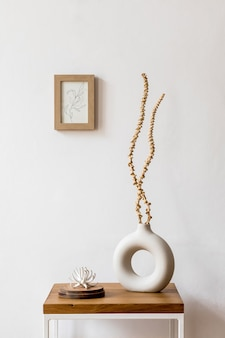 Composizione minimalista e di design di fiori secchi in vaso elegante, tavolino in legno, decorazione, cornice per foto e accessori all'interno bianco del soggiorno.