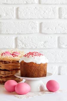 Composizione in pasqua minimalista con cesto di vimini e torta pasquale
