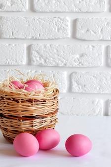 Composizione di pasqua minimalista con cesto di vimini e uova colorate di rosa su sfondo bianco. copia spazio
