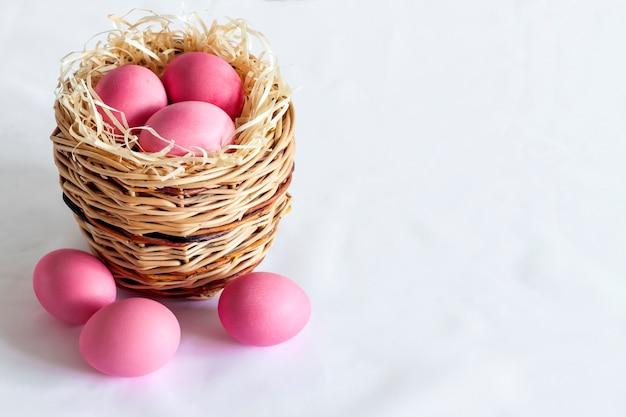 Composizione di pasqua minimalista con cesto di vimini e uova di colore rosa