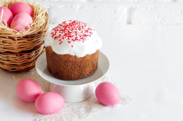 Composizione di pasqua minimalista con cesto di vimini con uova colorate di rosa e torta di pasqua su sfondo bianco. copia spazio