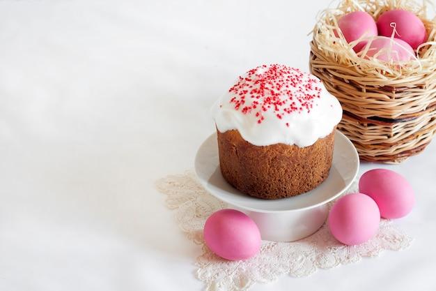 Composizione in pasqua minimalista con cesto di vimini con uova colorate di rosa e torta di pasqua su superficie bianca