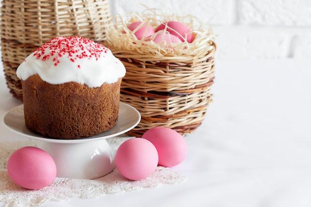 Composizione di pasqua minimalista con cesto di vimini con uova colorate di rosa e torta di pasqua