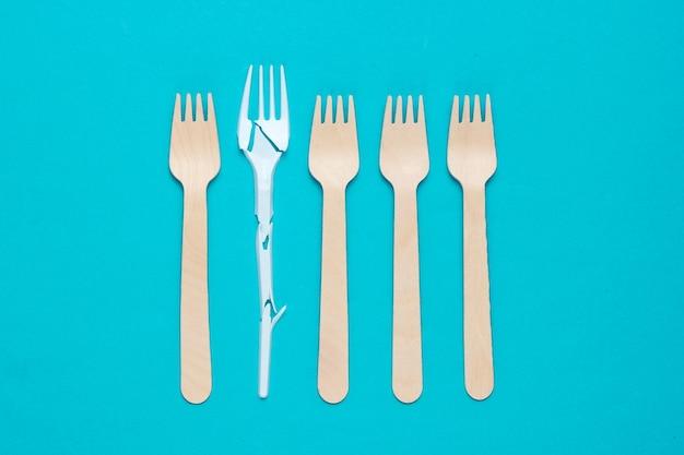Natura morta ecologicamente pulita minimalista. forchetta di plastica rotta tra molte forchette di legno su sfondo blu. posate realizzate con materiali naturali