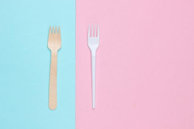 Concetto ambientale minimalista. forchette in legno e plastica su sfondo rosa pastello blu. sfondo eco creativo