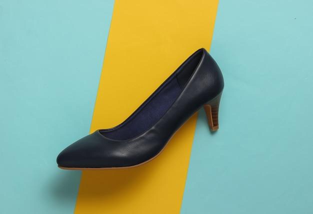 Concetto di moda minimalista scarpe in pelle da donna con tacchi su sfondo pastello giallo blu