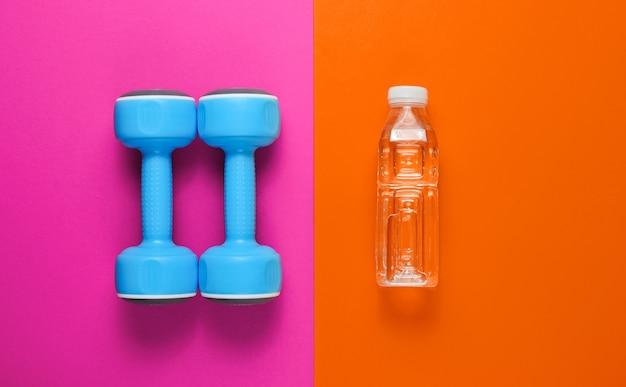 Concetto di fitness minimalista. manubri, bottiglia d'acqua colorata