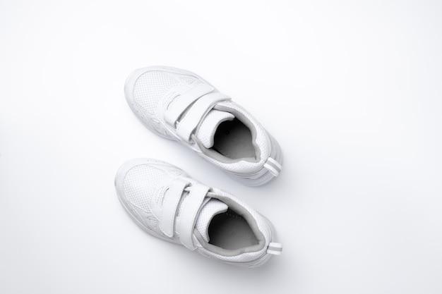Piatto minimalista per la pubblicità di scarpe sportive per bambini bianche con velcro isolato su un retro bianco...