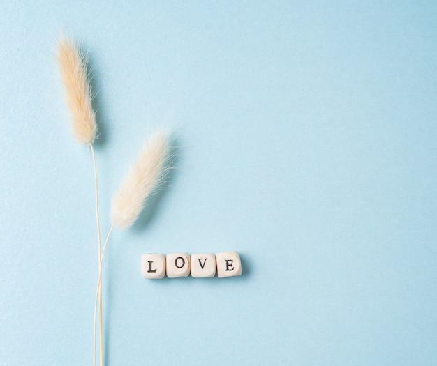 Piatto minimalista giaceva con fiori secchi bianchi e cubetti con la parola amore su sfondo blu. concetto di san valentino, festa della mamma, giorno del matrimonio. vista dall'alto e copia spazio
