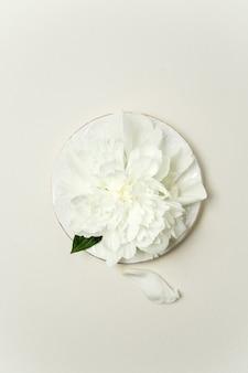 Composizione floreale minimalista. fiore di peonia bianca e petali su un piatto bianco su sfondo pastello, vista dall'alto