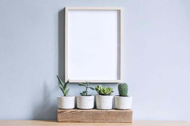 Interno di casa minimalista con cornice per foto sul tavolo marrone con composizione di cactus e piante grasse sul pezzo di legno in eleganti vasi di cemento