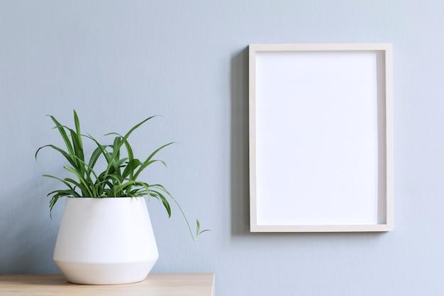 Interno di casa minimalista con cornice per foto sul tavolo marrone con pianta