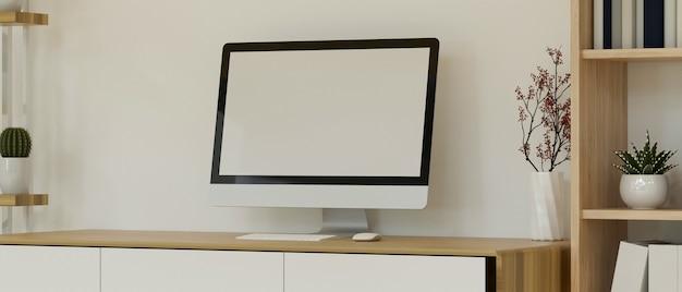 Interno minimalista del posto di lavoro domestico con il modello dello schermo in bianco del computer desktop contro la parete bianca