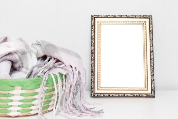 Design degli interni minimalista con cornice per foto e cesto con caldi vestiti di lana su una scrivania