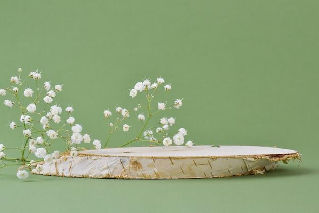Una scena minimalista di un albero abbattuto giace con fiori su una superficie naturale