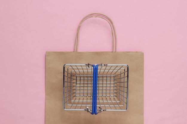 Concetto di acquisto minimalista sacco di carta del cestino della spesa su sfondo rosa pastello