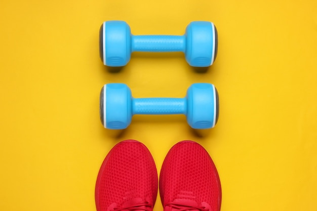Natura morta di sport minimalista. abbigliamento sportivo. scarpe sportive rosse per allenamento e manubri in plastica blu su sfondo giallo.