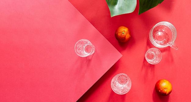 Natura morta minimalista di frutta arancione e bicchieri d'acqua sul tavolo rosso