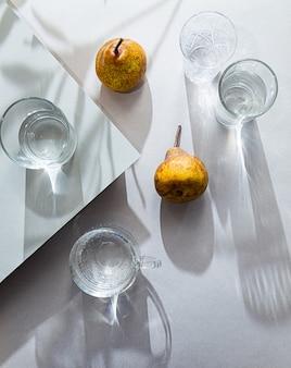 Natura morta minimalista di pere e bicchieri d'acqua vista dall'alto
